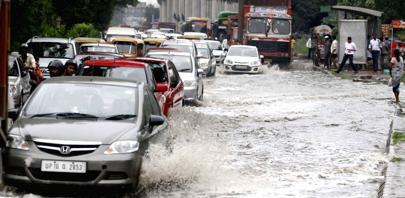 Vehicles struggle through a flooded road in Okhla of Delhi on Aug 10, 2014.