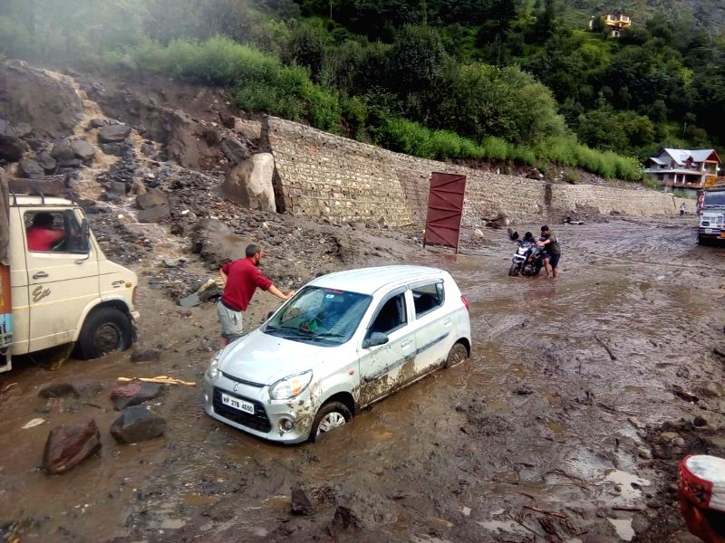 Vehicles struggle through a marshy stretch after a cloud burst occurred near Manali on July 18, 2018.