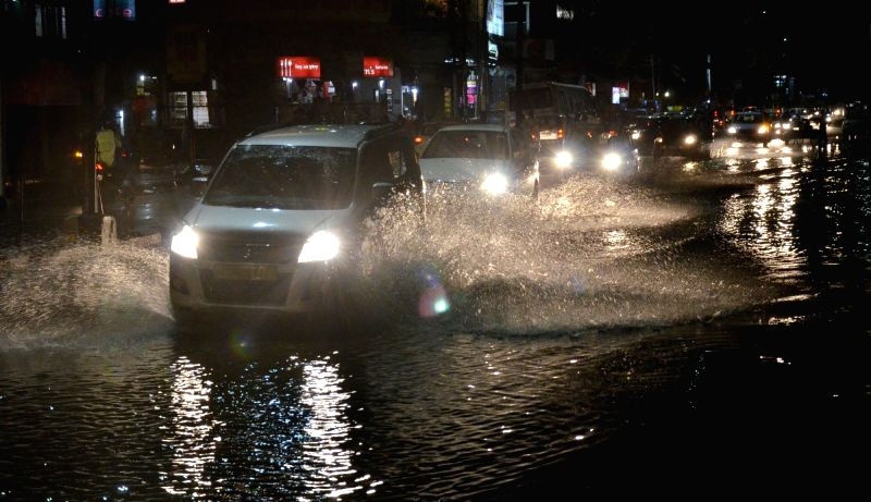 Vehicles struggle through a waterlogged road, after heavy rains lashed Guwahati on July 14, 2018.