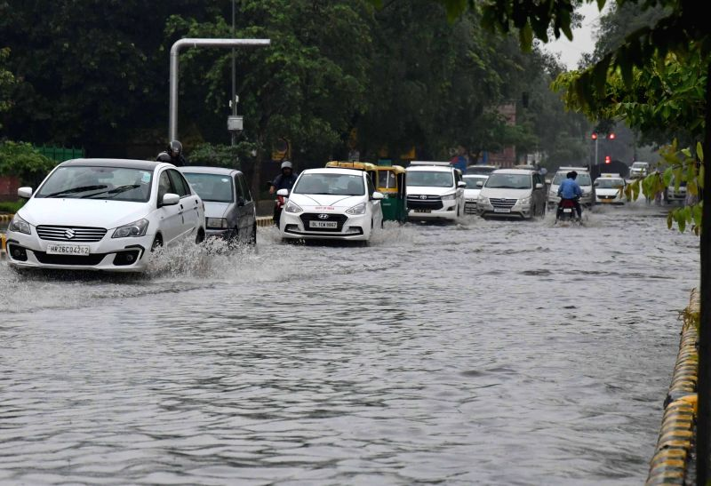 Vehicles struggle through a waterlogged street in New Delhi, after heavy rains lashed the national capital on July 13, 2018.