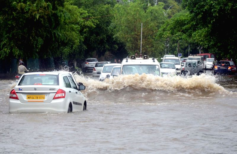 Vehicles struggle through a waterlogged street, in Bhopal, on July 17, 2018.