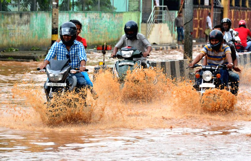 Vehicles struggle through the waterlogged streets of Guwahati after heavy showers on Aug 10, 2014.