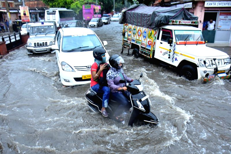 Vehicles struggle through water logged streets of Jaipur, on Aug 2, 2016.