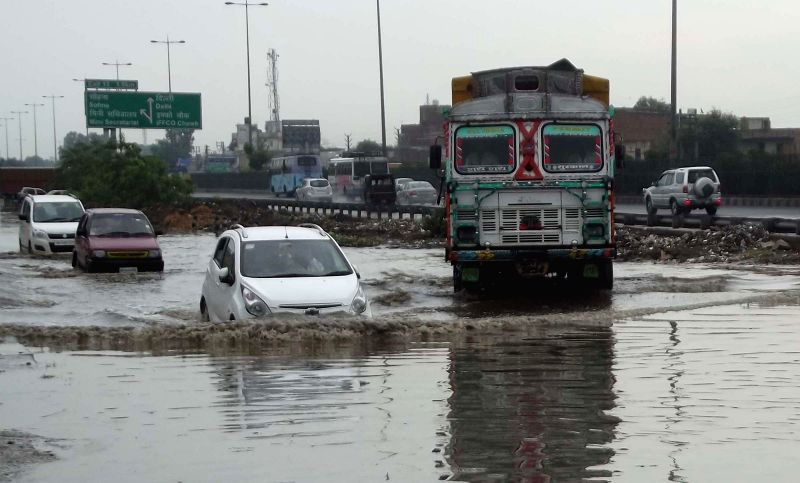 Vehicles struggle through waterlogged National Highway-8 as heavy rains lashed Gurgaon on Aug 31, 2014.