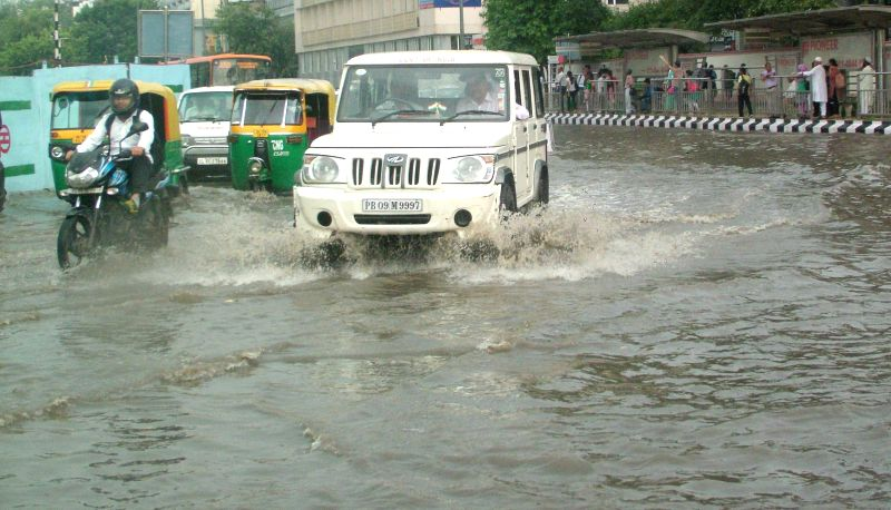 Vehicles struggle through waterlogged streets of New Delhi near ITO after heavy rains lashed the national capital on Aug 31, 2014.