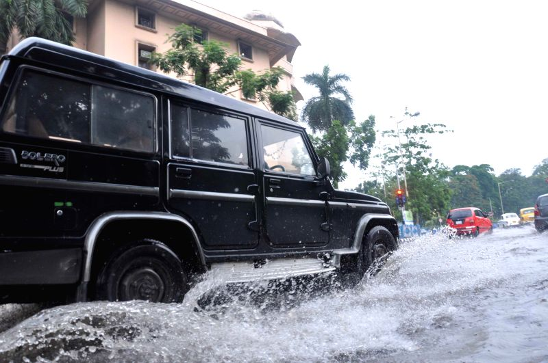 Vehicles wade through water logged roads after heavy rains in Kolkata on June 17, 2014.