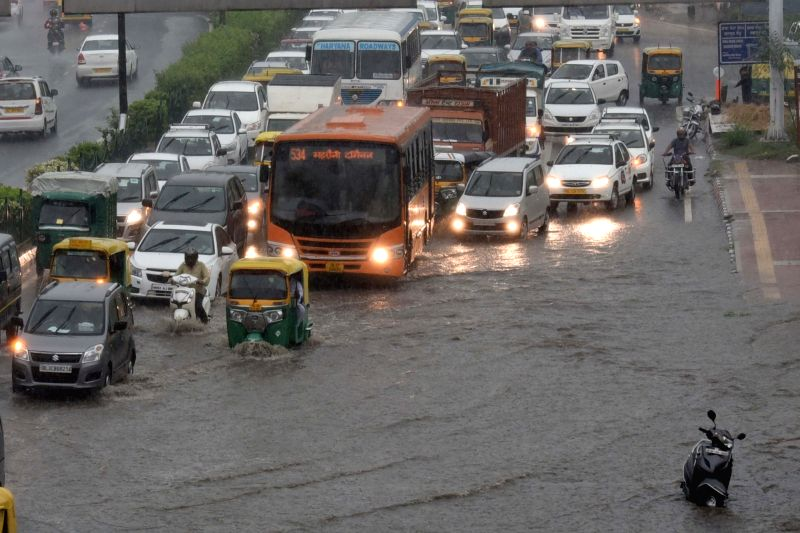 Vehicular movement slows down in New Delhi due to water logging after heavy rains lashed the national capital on July 13, 2018.