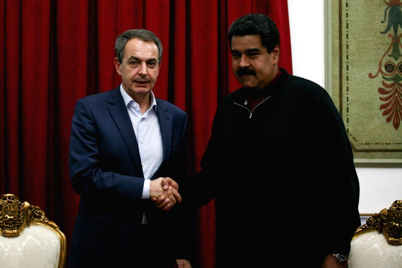Venezuelan President Nicolas Maduro (R) shakes hands with former Spanish Prime Minister Jose Luis Rodriguez Zapatero, guest of the Venezuelan National Electoral ... - Jose Luis Rodriguez Zapatero