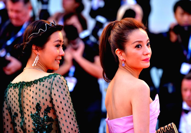 """Cast members of the movie """"Dearest"""" Zhao Wei (R) and Hao Lei pose on the red carpet during the """"Birdman"""" premiere and the opening ceremony of the"""