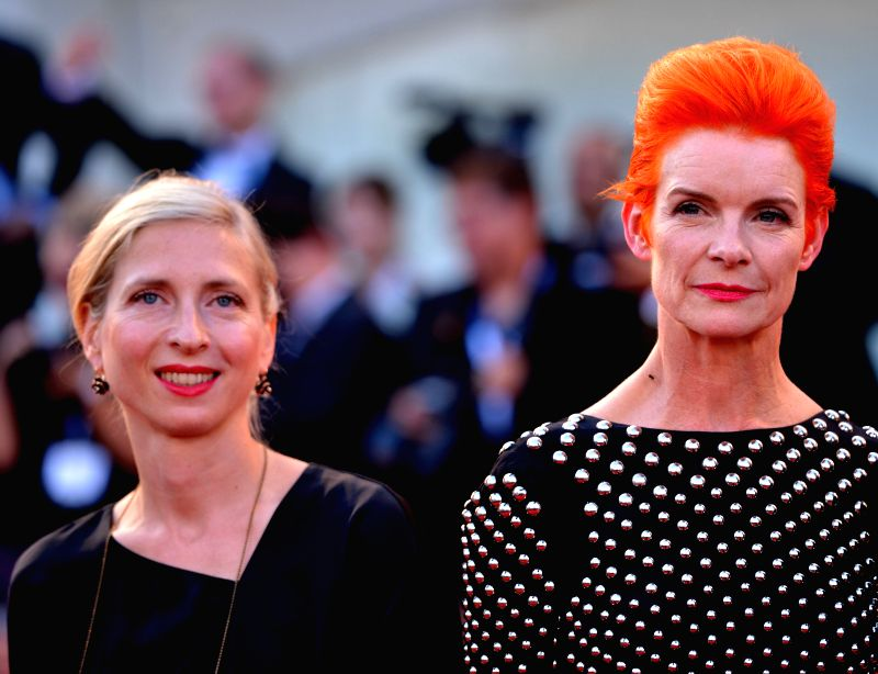 """Member of the jury Sandy Powell (R) poses on the red carpet during the """"Birdman"""" premiere and the opening ceremony of the 71st Venice International Film ..."""