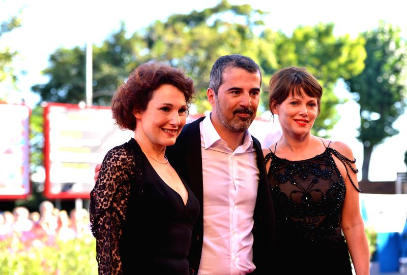 "Director Francesco Munzi (C) and cast members Anna Ferruzzo (L), Barbora Bobulova pose on the red carpet for the film ""Anime Nere"" (Black Souls) during the"