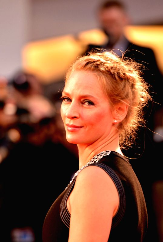 """US actress Uma Thurman poses on the red carpet for """"Il giovane favoloso"""" which is selected for the main competition during the 71st Venice Film Festival, .."""