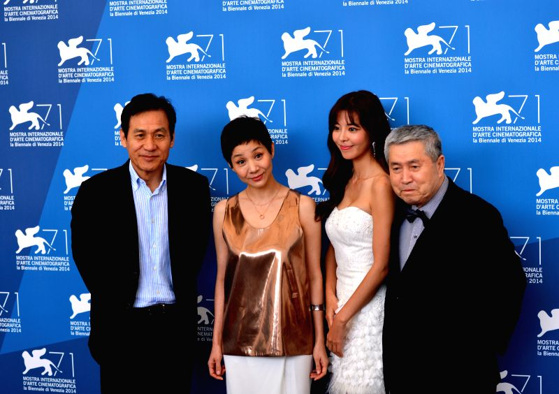 "South Korean director Im Kwon-taek (1st R) and cast members pose at the photocall for the movie ""Revivire"" during the 71st Venice Film Festival, in Lido of"