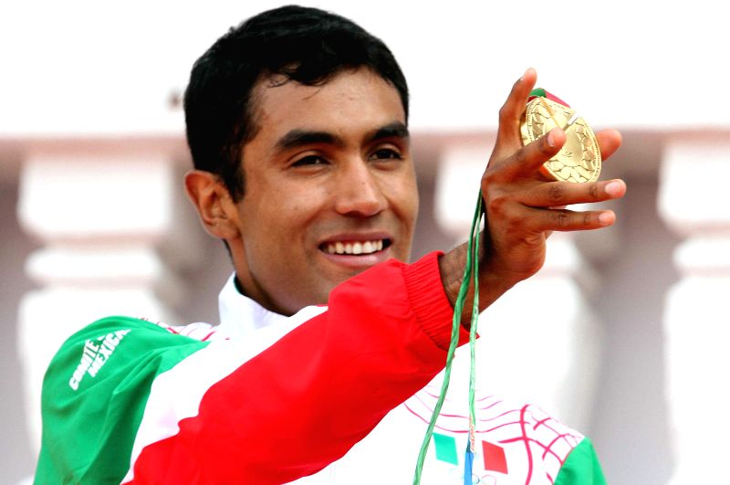Mexico's Juan Luis Barrios poses with the gold medal during the awarding ceremony of the 5000m athletics competition in the 2014 Veracruz Central American and Caribbean Games in Boca del ...