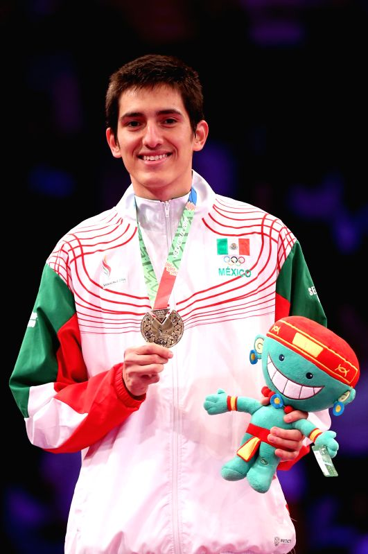 Mexico's Saul Gutierrez poses on the podium during the awarding ceremony of the men's 63kg taekwondo in the 2014 Veracruz Central American and Caribbean Games in Boca del Rio, Veracruz, ...