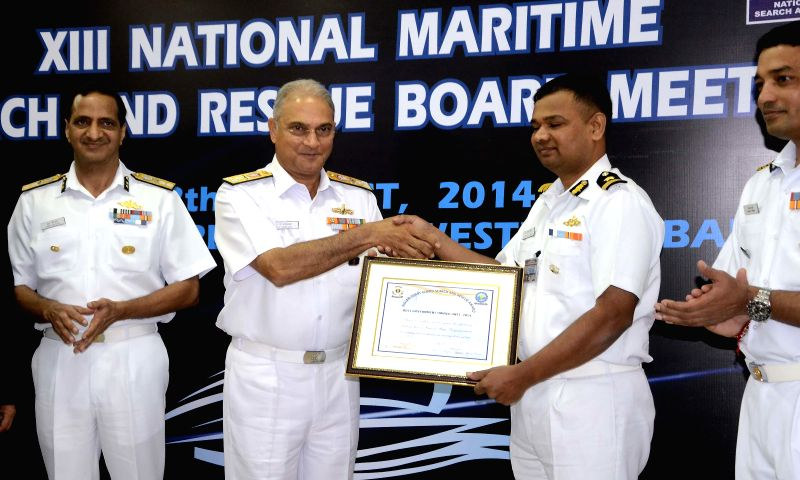 Vice Admiral Anurag G Thapliyal,AVSM and Bar, Director General Indian Coast Guard felicitates a soldier during XII National Maritime Search and Rescue (NMSAR) Board Meeting in Mumbai on Aug 12, 2014.