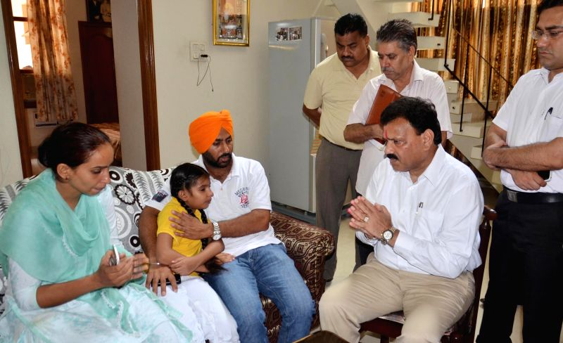 Vice-chairman of the National Commission for Scheduled Castes Dr Raj Kumar Verka meets family members of 5-year-old boy Harshbir Singh who has been kidnapped, in Amritsar on Aug 7, 2014.