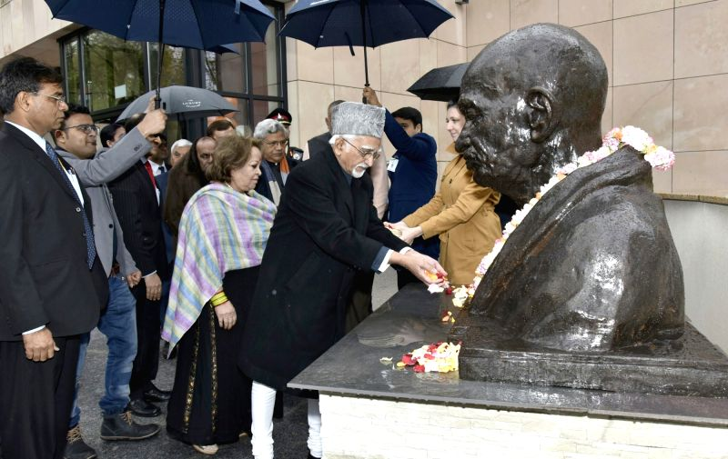 Vice President M Hamid Ansari pays tributes to Mahatma Gandhi, at the Embassy of India Complex, in Warsaw, Poland on April 28, 2017. Also seen Salma Ansari.