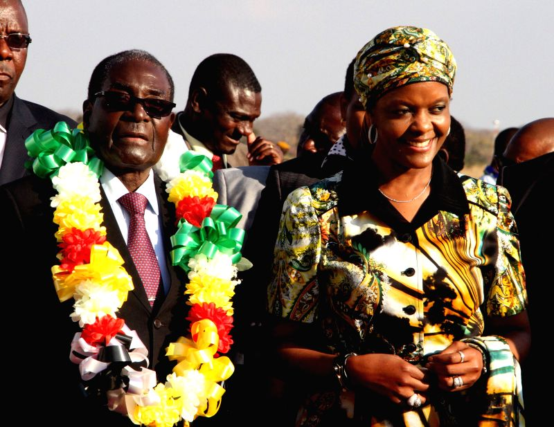 Zimbabwean President Robert Mugabe (L) greets leaders from Southern African Development Community (SADC) nations at the airport of Victoria Falls in Victoria