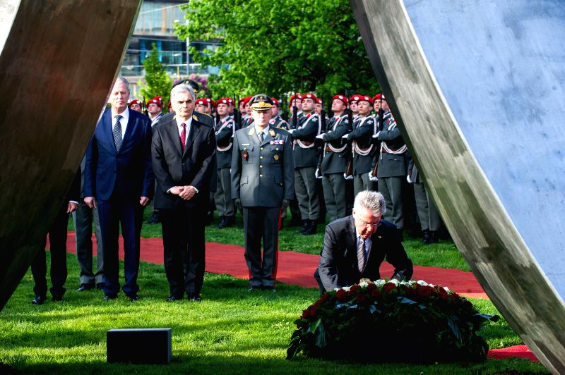 Austrian President Heinz Fischer (front) offers a wreath in front of the monument commemorating the 70th anniversary of the re-establishment of the Republic of ...