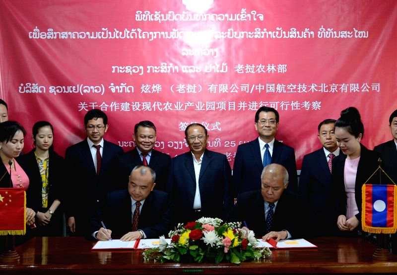 VIENTIANE, April 26, 2017 - Representatives from Lao Ministry of Agriculture and Forestry (R, front) and China's Xuanye (Laos) Co., Ltd/AVIC International Beijing Co., Ltd (L, front) sign a ...
