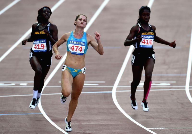 Viktoriya Zyabkina(C) of Kazakhstan passes the finish line in Women's 100m Final at the 28th Summer Universiade in Gwangju, South Korea, on July 9, 2015. Viktoriya ...