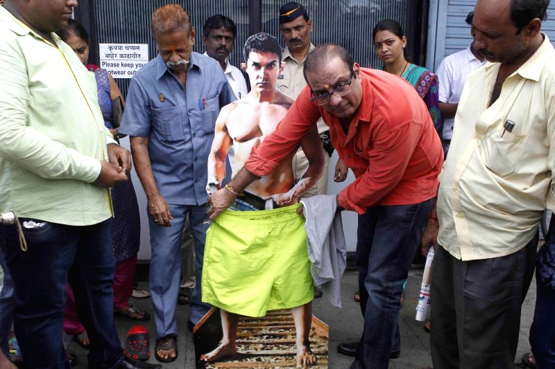 Vile Parle Congress legislator Krishna Hegde protested against Aamir`s nudity by `dressing` up the actor`s nude posters of his forthcoming movie ``PK`` in Mumbai on Aug 9, 2014.
