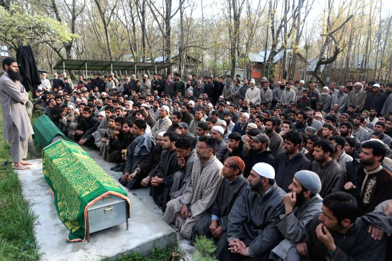 Villagers at the funeral of sarpanch Gh Nabi Mir and his son Firdous Ahmad Mir who were killed by militants last night at Batigund Trail in Pulwama district of Jammu and Kashmir on April 22, 2014.