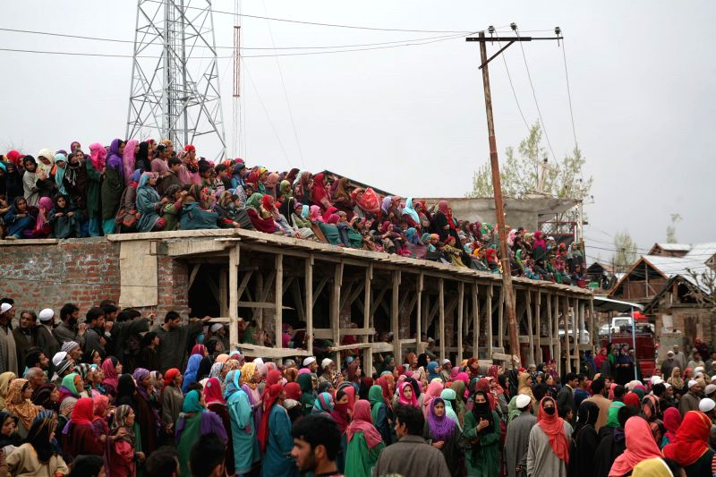 Villagers gather around the body of a militant during his funeral procession at Kellar in Shopian District of Jammu and Kashmir on April 26, 2014.