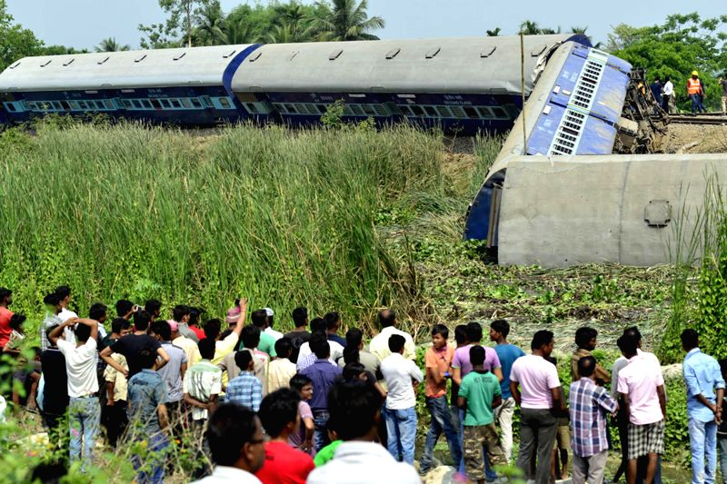 Villagers gather near the derailed bogies of BG Express at Ajuri station near Morigaon in central Assam, about 80km away from Guwahati on April 16, 2014. More than 50 passengers were injured in the ..