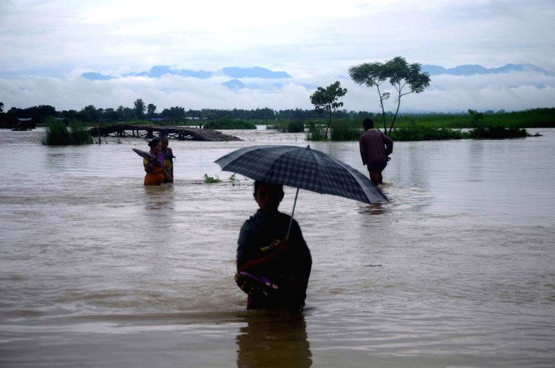 Villagers move to higher lands as water from Saralbhanga river inundates six villages of Dotma block in Assam's Kokrajhar district on Aug 16, 2014. Saralbhanga river is a tributary of Brahmaputra ...
