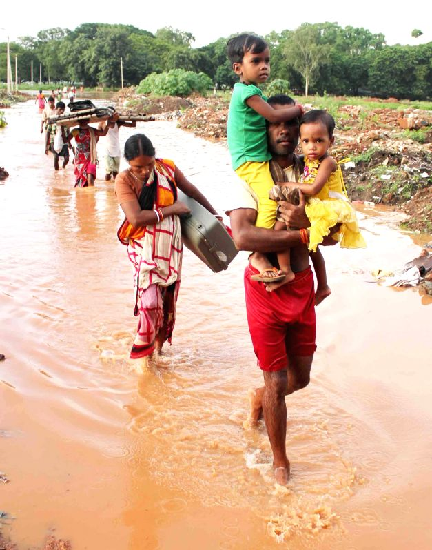 Villagers move to higher places as water from Kathajodi river inundated their village in Cuttack district of Odisha on Aug 7, 2014.