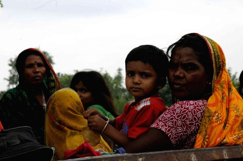 Villagers move towards higher lands near Indo- Nepal border at Birpur in wake of Kosi flood alerts in Supaul district of Bihar on Aug 3, 2014.