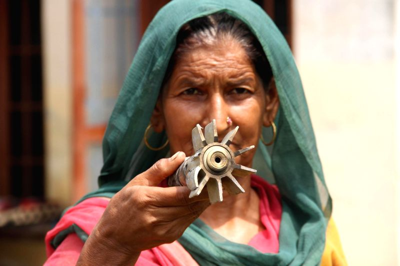 Villagers show shells fired on their village allegedly from Pakistan in R S Pura Sector of Jammu and Kashmir near Indo-Pakistan border on Aug 22, 2014.