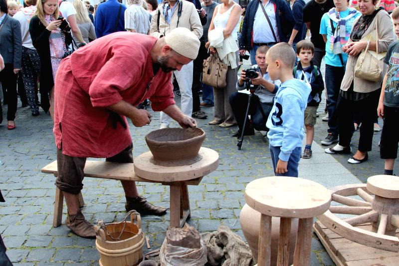 A craftsman makes pottery on the Bartholomew Fair in Vilnius, Lithuania, on Aug. 22, 2014. The two-day fair kicked off here on Friday, bringing ironware, wooden ...