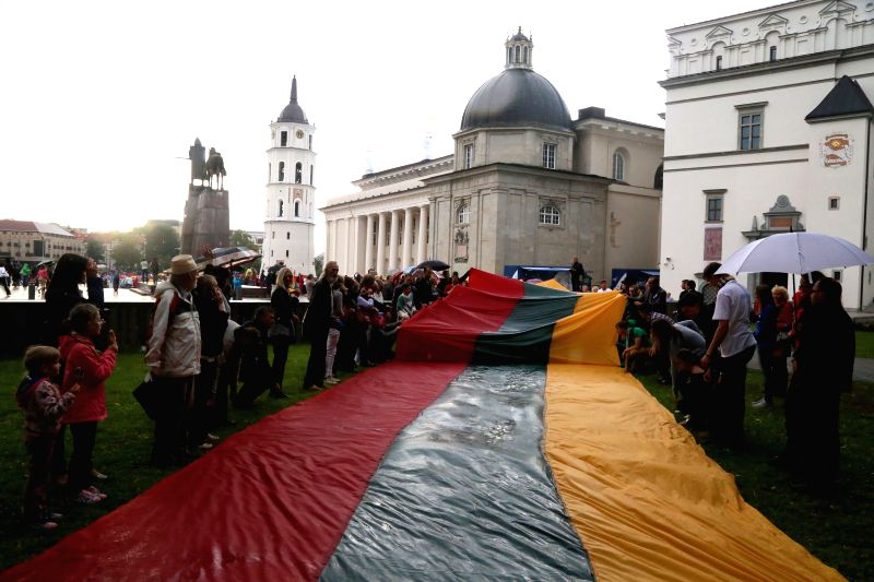 Four Lithuanian national flags with a total length of 1 km are carried into the cathedral square on an activity marking the 25th anniversary of Baltic Way in ...