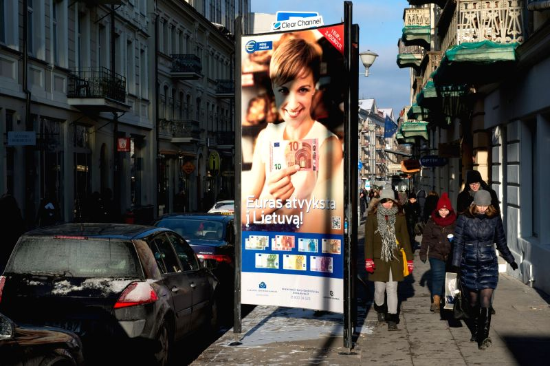 People walk past a poster of Euro on a street in Vilnius, Lithuania, on Dec. 30, 2014. Lithuania will join the euro zone on Jan. 1, 2015, as the 19th member country