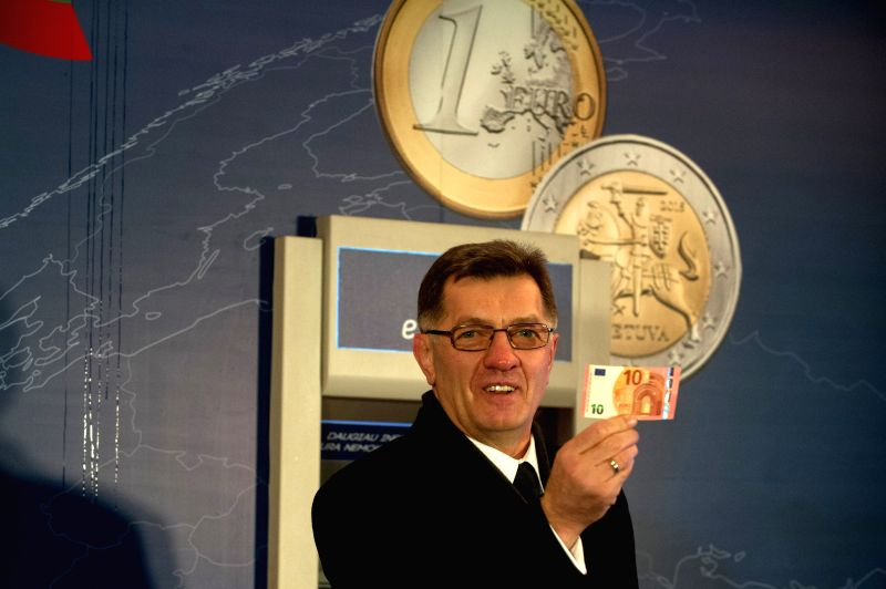 Lithuania's PM Algirdas Butkevicius shows a 10-euro note in Vilnius, Lithuania, on Jan. 1, 2015. Lithuania joined the euro zone on Jan. 1, 2015, as the 19th member ..