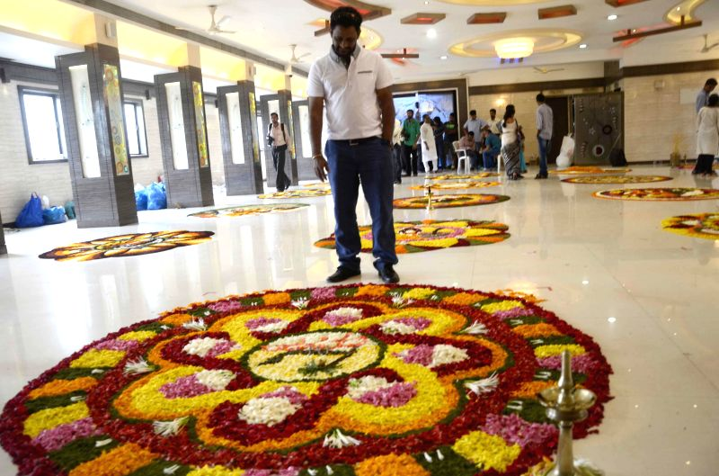 Visitors look at a flower-rangoli during a flower-rangoli competition ahead of Onam in Mumbai on Aug 24, 2014.