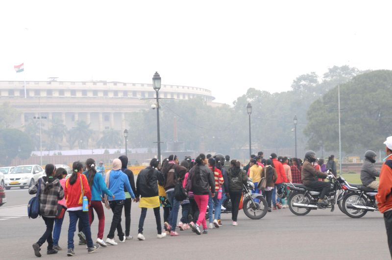 Visitors near the Parliament House on a chilly morning in New Delhi on Dec. 13, 2014. It was a chilly Saturday morning in the national capital with the minimum temperature recorded at 10.4 degrees ...
