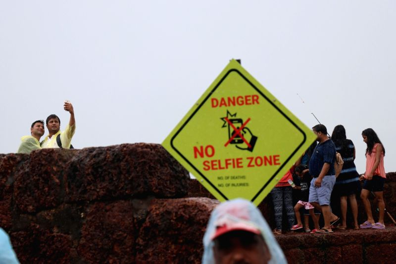 "Visitors pose for selfies despite of a board stating""Danger, No Selfie Zone"" put up at Aguada fort in Goa's Sinquerim on July 12, 2018. Amid a spate of drownings and accidents ..."