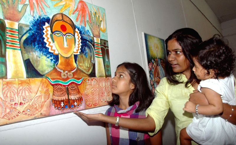 """Visitors seen at the """"SPOORTHY"""" an exhibition of paintings by Harapanahalli Ragavendra, at Venkatappa Art Gallery, in Bangalore on May 3, 2014."""