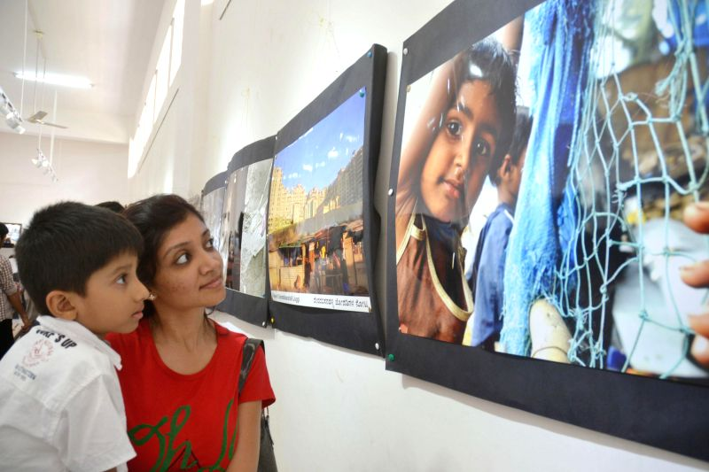 Visitors seen enjoying a unique photo exhibition by Sudhir Shetty at Rangoli Art Metro Railway Station at MG Road, in Bangalore on June 21, 2014.