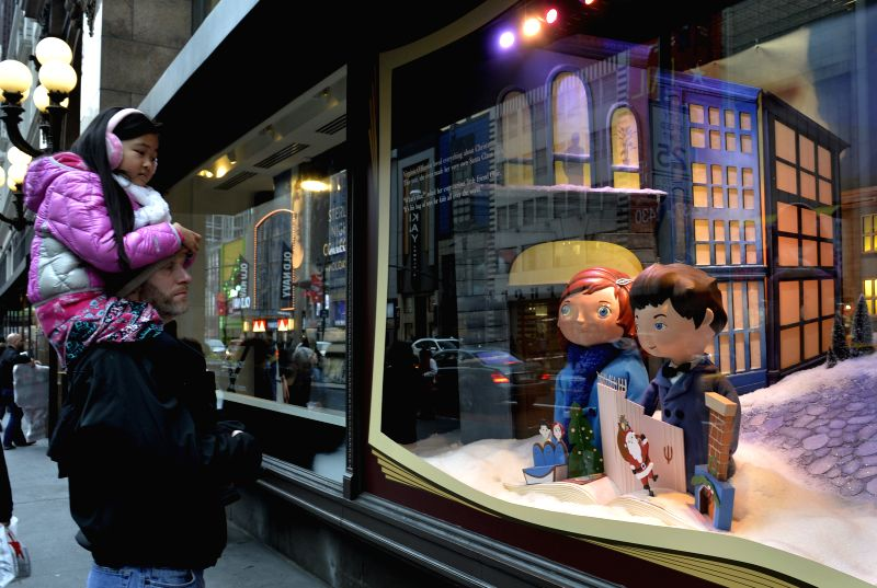 Visitors watch the Macy's holiday windows in Manhattan, New York City, the United States, Dec. 9, 2015. Macy's holiday windows, revealed before the Christmas ...