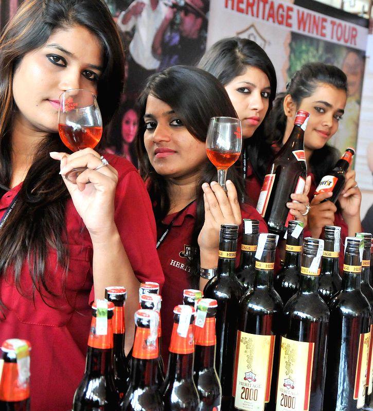 Volunteers display wine during  Bangalore International Wine Festival organised by Karnataka Wine Board in Bangalore on July 25, 2014.