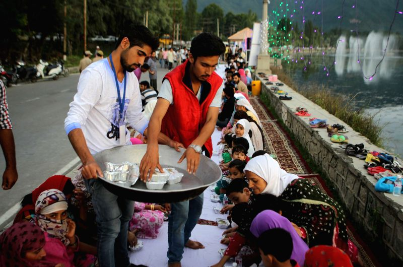 Volunteers distribute food to Kashmiri Muslims as they wait to break their Ramadan fast on the bank of Dal Lake in Srinagar, summer capital of Indian-controlled ...