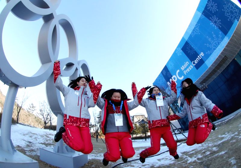 Volunteers for the Feb. 9-25 PyeongChang Winter Olympics pose for a photo in front of the main press center in the host town of PyeongChang, some 180 kilometers east of Seoul, on Jan. 29, ...