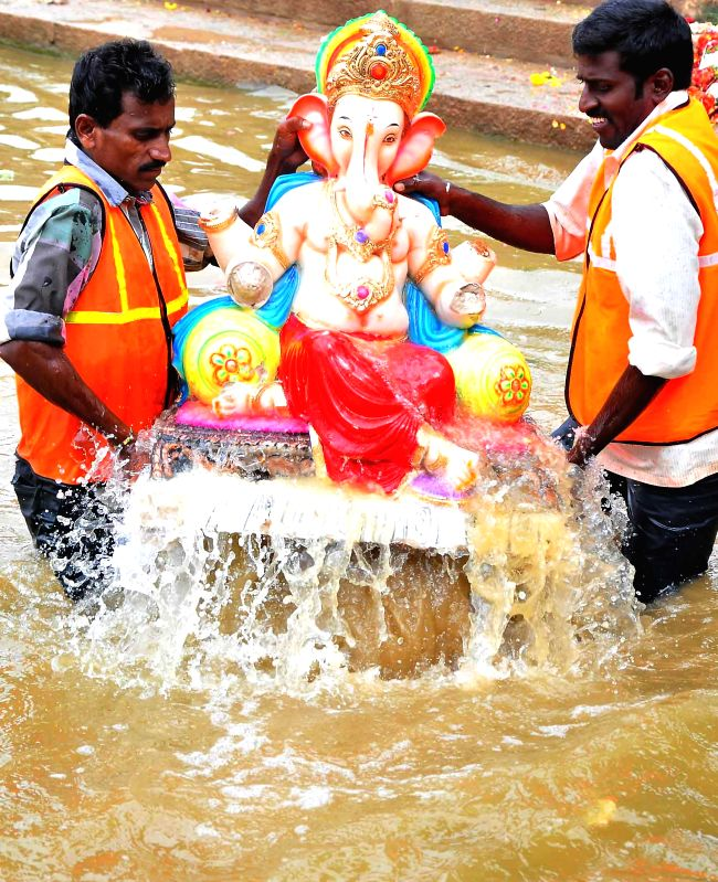 Volunteers immersing Ganesha idols, celebrating Ganesha Chaturthi Festival, at Ulsoor Lake in Bangalore on Aug. 30, 2014.
