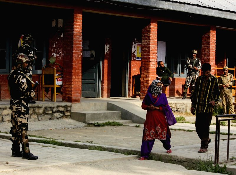 Voters come out of a polling booth after casting their votes amid tight security during the seventh phase of 2014 Lok Sabha Polls in Srinagar on April 30, 2014.