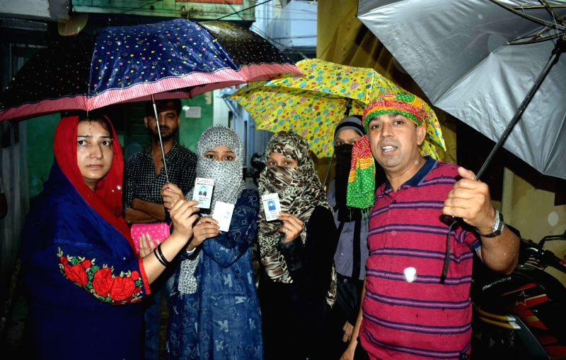 Voters show their voter ID cards as they wait in a queue to cast their vote at a polling booth during Patna Municipal Corporation elections on June 7, 2017.